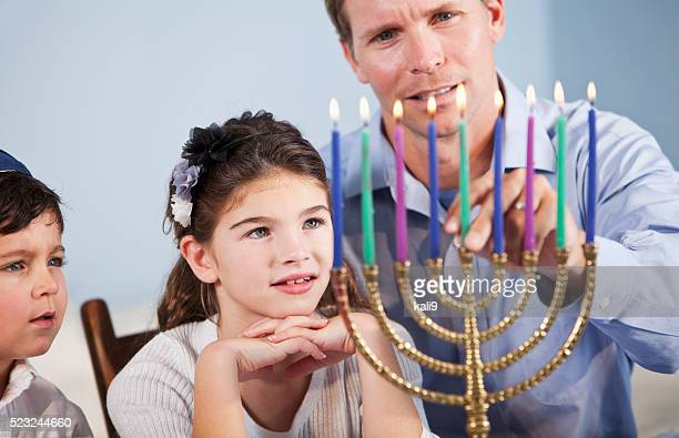 Children watching father light Hanukkah Menorah