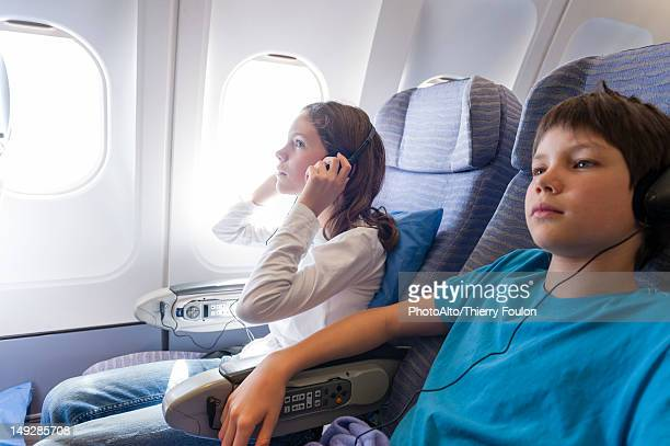 Children watching movie on airplane with headphones