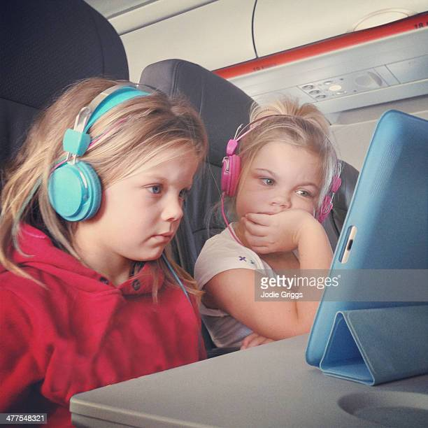 Children watching movie on tablet whilst flying