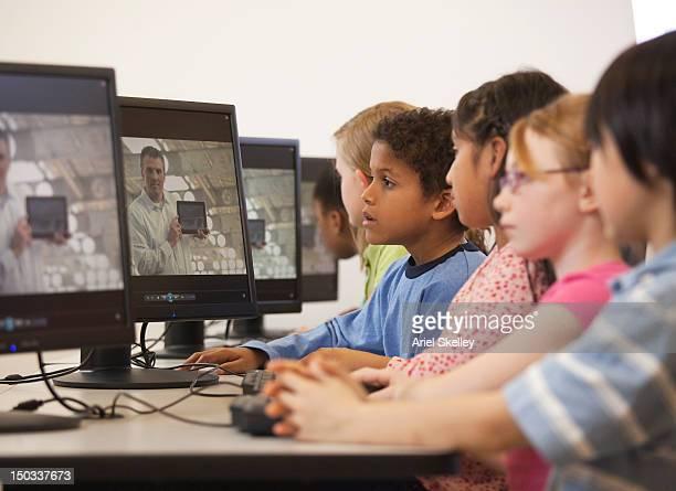 Kinder beobachten online-Unterricht im Computerraum