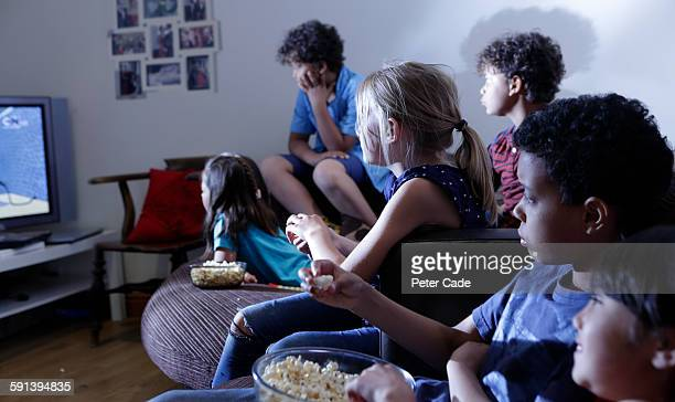Children watching television in dark room