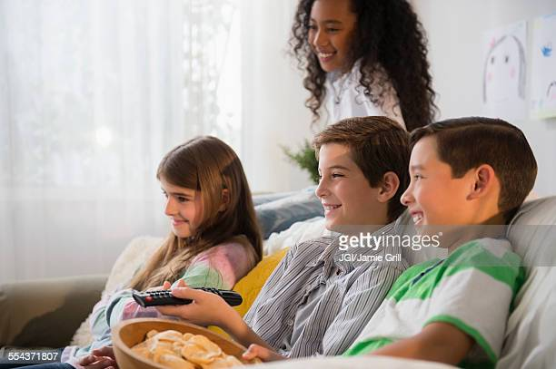 children watching television on sofa - children only stock photos and pictures