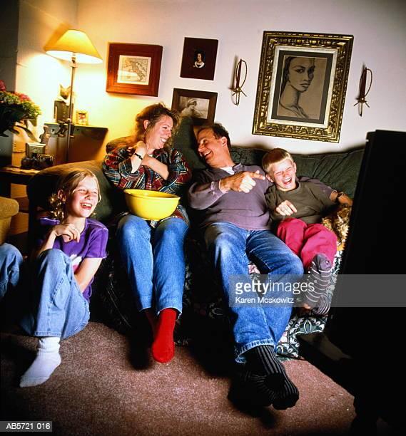 children (6-10) watching television with parents, smiling - nordeuropäischer abstammung stock-fotos und bilder