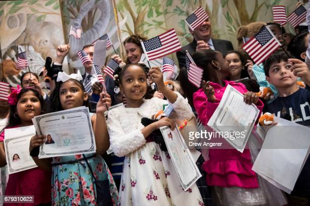 Children wave American flags and hold their certificates of citizenship after becoming US citizens during a citizenship ceremony at The Bronx Zoo May...