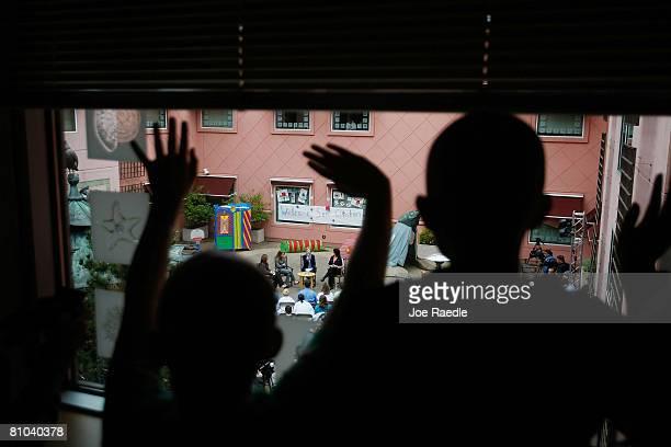 Children wave as Democratic presidential hopeful U.S. Senator Hillary Clinton sits with Jeannie Roberts, Jordan Kokich and Bridget Sheffler as she...
