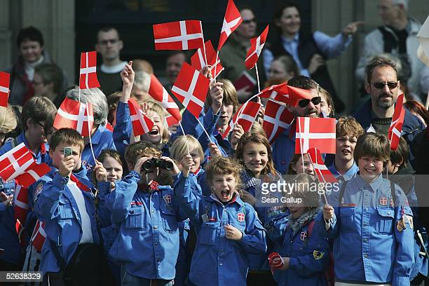 Children wave Danish flags in front of the Amalienborg Palace April 16 2005 in celebration of the Queen's 65th birthday in Copenhagen Denmark