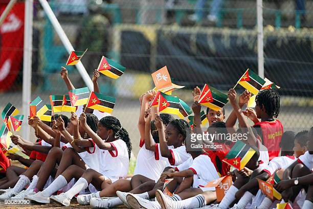 Children wave flags as they watch the 2010 World Cup Qualifier match between Mozambique and Tunisia at the Estadio Nacional da Machava on November 14...