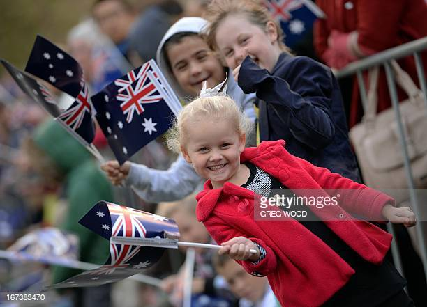 Children wave flags as they watch the Anzac Day march through Sydney on April 25 2013 Tens of thousands of Australians and New Zealanders turned out...