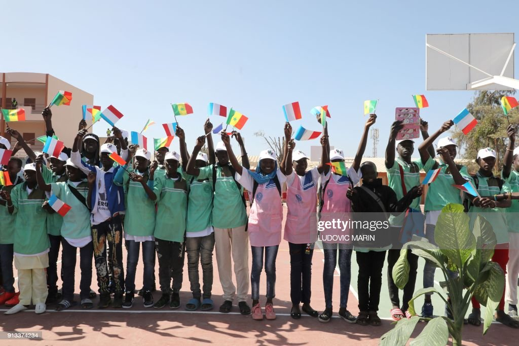 Children wave french and senegalese flags as they greet the french children wave french and senegalese flags as they greet the french and senegalese presidents during the inauguration of the bel air secondary school in m4hsunfo
