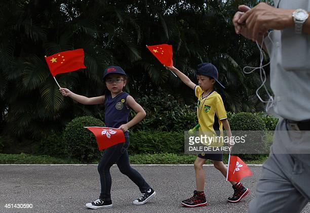 Children wave Hong Kong and Chinese national flags during an open day at the Chinese People's Liberation Army Shek Kong Barracks in Hong Kong on June...