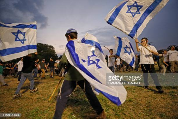 Children wave Israeli flags during a gathering in the settlement of Mehola in the Jordan valley in the occupied West Bank, on February 3 to welcome a...