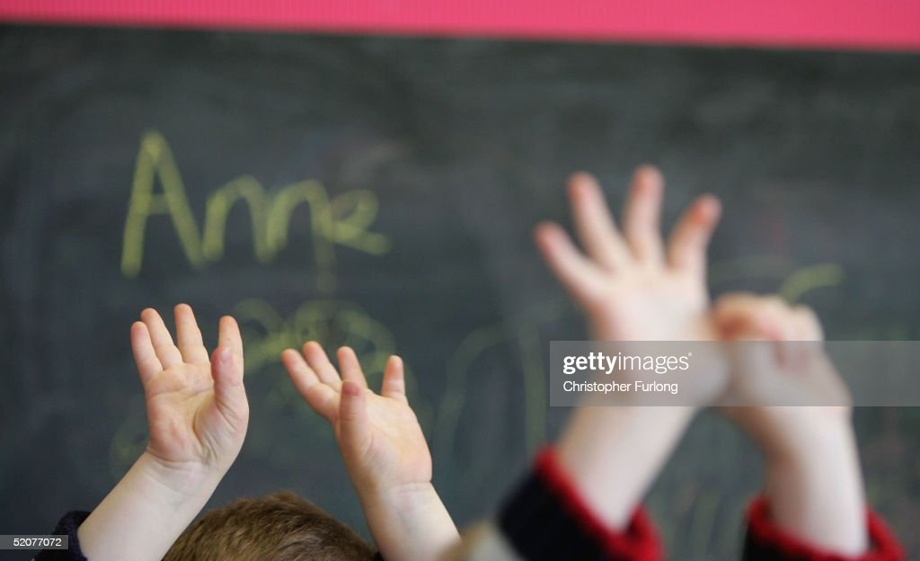 Children wave their hands at a private nursery school January 28, 2005 in Glasgow, Scotland. The average price of pre-school care has increased over the past year, sending child care prices to an average of GBP200 in parts of the southeast. Many working parents in the UK have called for pre-school childcare subsidies such as those in France where nearly 100% of three-year-olds are in pre-school education, despite the fact that school attendance is not compulsory until they turn five.