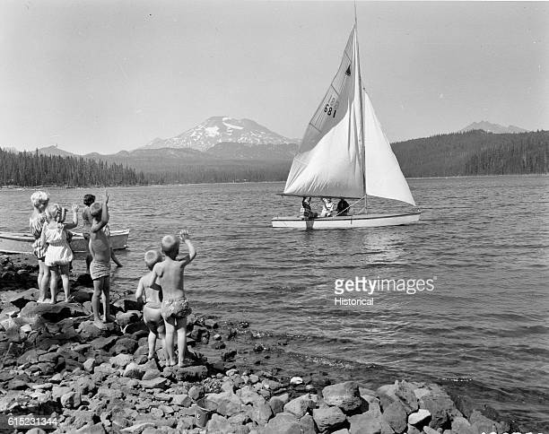 Children wave to some people on a sailboat on Elk Lake in Deschutes National Forest, Oregon. The South Sister can be seen in the background.