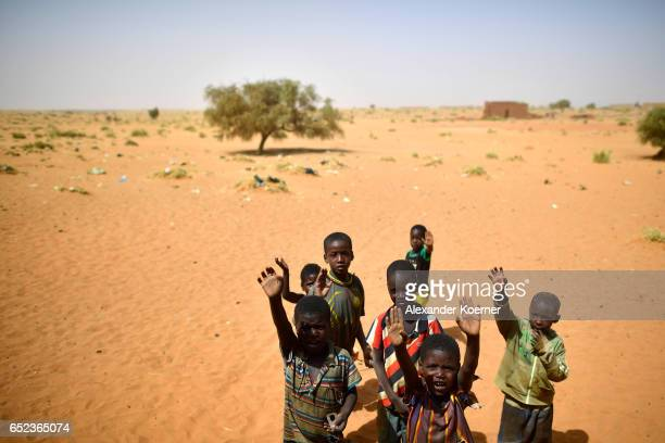 Children wave towards soldiers of the Bundeswehr after leaving a weekly cattle market on the outskirts of Gao on March 7 2017 in Gao Mali The...