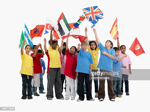 children waving flags - global village stock pictures, royalty-free photos & images