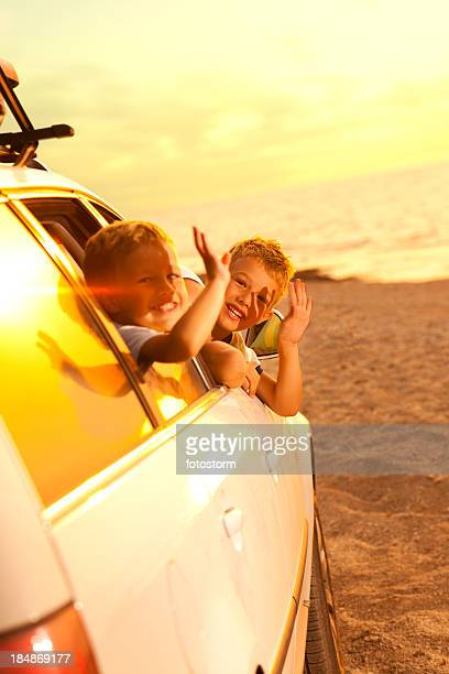 Children waving from car as they arrive at beach