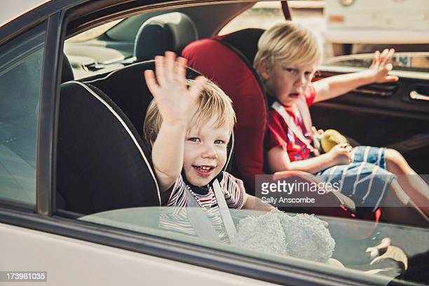 Children waving from in the car