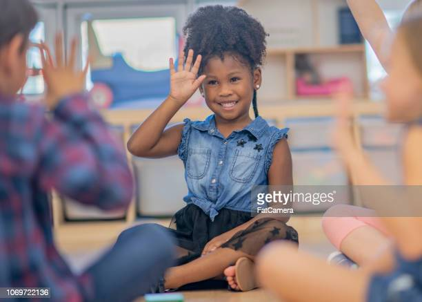 children waving in kindergarten class - waving gesture stock photos and pictures