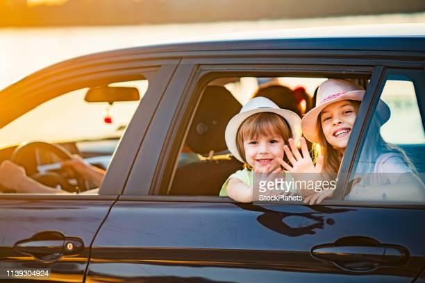 enfants agitant par la fenêtre de voiture - commencement photos et images de collection