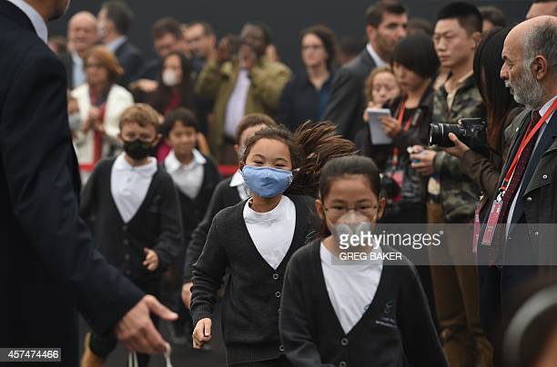 Children wear masks to protect from pollution as they run out after performing at the groundbreaking ceremony for the new French International School...