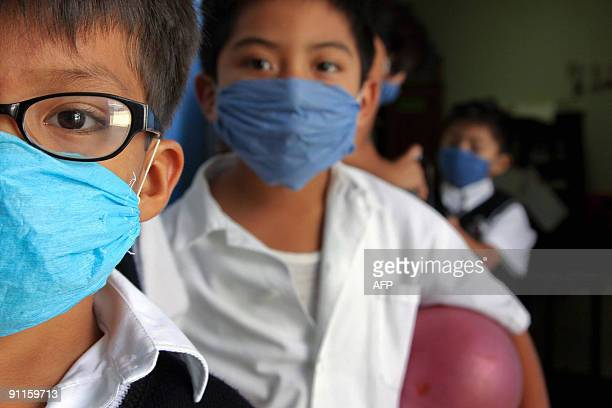 Children wear surgical masks at 'Enrique Rebsamen' school in Oaxaca Mexico on September 25 2009 Three cases of Influenza A virus were confirmed in...