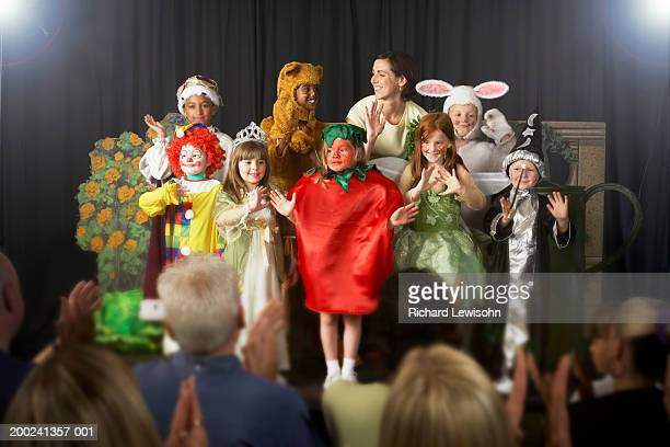 children (4-9) wearing costumes and teacher waving on stage - uitvoerende kunst voorstelling stockfoto's en -beelden