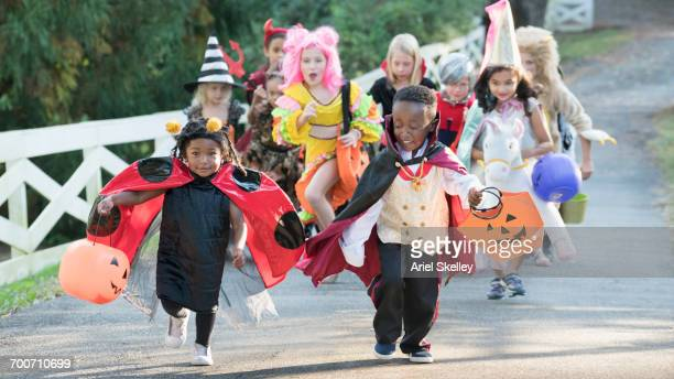 children wearing costumes on halloween running in park - halloween kids stock photos and pictures