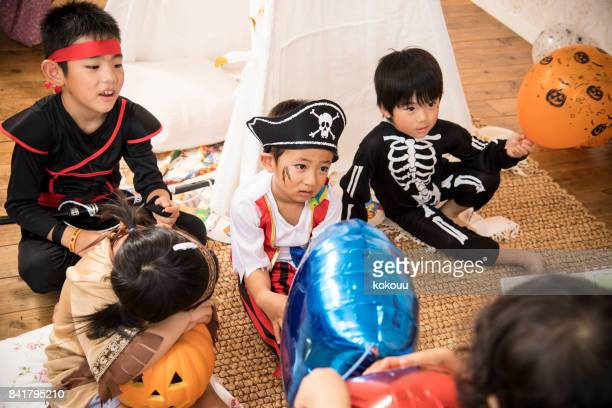 Children wearing costumes talk in the room.