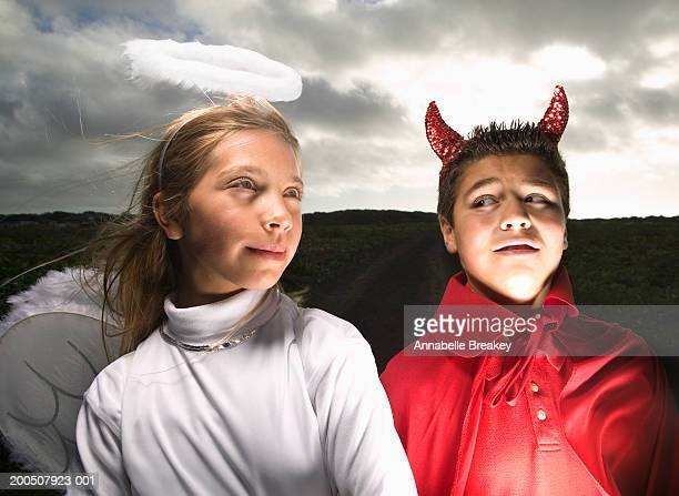 children (10-12) wearing devil and angel costumes in field - evil angel photos et images de collection