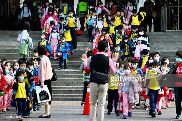 Children wearing face masks leave their elementary school at the end of the day in Xindian district, New Taipei City on March 3, 2020. - The world...