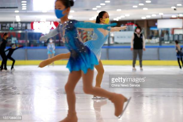 Children wearing face masks take part in a figure skating training session at an ice rink on May 25 2020 in Beijing China