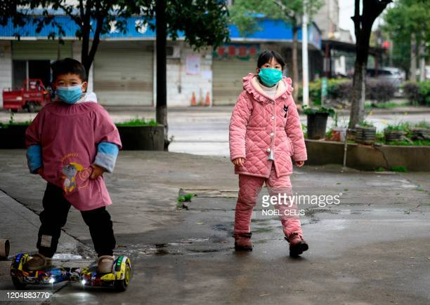 Children wearing face masks walk along a street in Yueyang, Hunan province on March 3, 2020. - The world has entered uncharted territory in its...