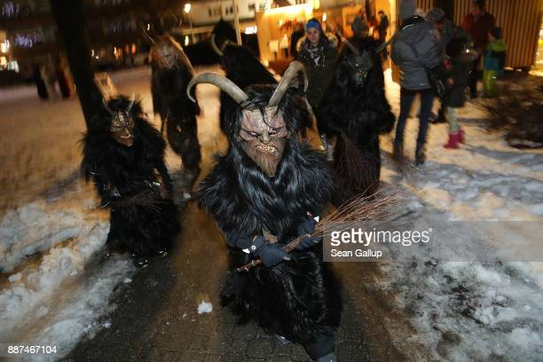 Children wearing horned wooden masks and dressed as the Krampus creature visit a Christmas market prior to the annual Krampus parade on Saint...