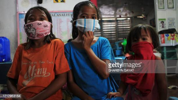 Children wearing improvised face masks take shelter at a school building serving as evacuation center in Sorsogon town Bicol region south of Manila...