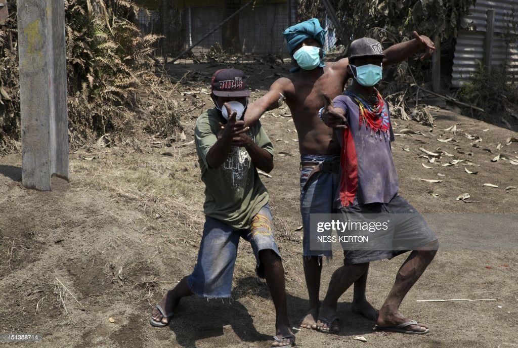 Children wearing masks plays among ash following the eruption of Mount Tavurvur in eastern Papua New Guinea on August 30, 2014. A volcano which has erupted in Papua New Guinea was on August 30 spewing fragments from its crater and rumbling loudly, but its activity appeared to be subsiding, a seismologist said. Mount Tavurvur, which destroyed the town of Rabaul when it erupted simultaneously with nearby Mount Vulcan in 1994, came to life again early Friday, with rocks and ash erupting from its centre.