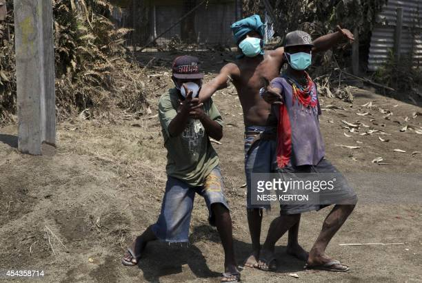 Children wearing masks plays among ash following the eruption of Mount Tavurvur in eastern Papua New Guinea on August 30 2014 A volcano which has...
