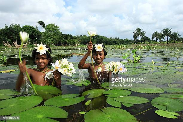 Children wearing ornaments made of water lily the national flower of Bangladesh Jessore Bangladesh September 16 2007