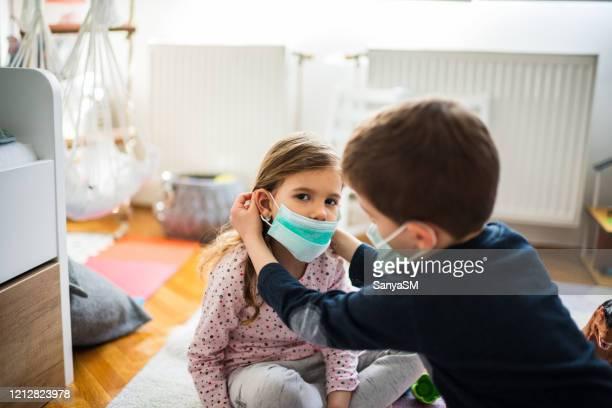 children wearing pollution masks at home - mascherina antipolvere foto e immagini stock