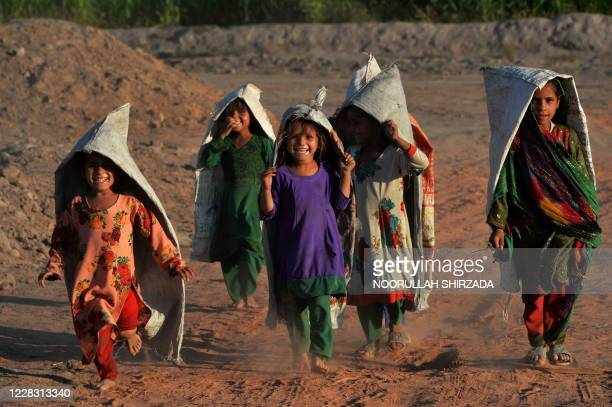 Children wearing sacks as play along a dusty road on the outskirts of Jalalabad on September 2, 2020.
