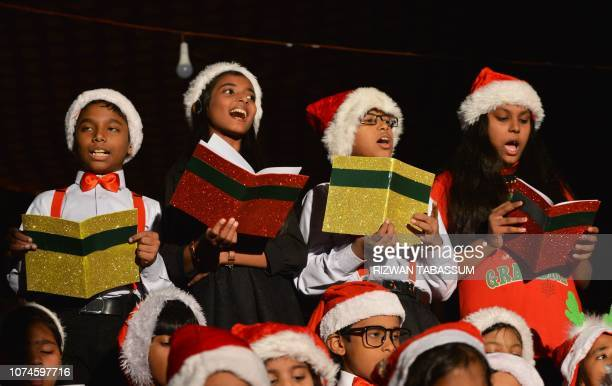 Children wearing Santa Claus costumes sing in a choir during a Christmas service at Saint Patrick's Cathedral in Karachi on December 22 2018