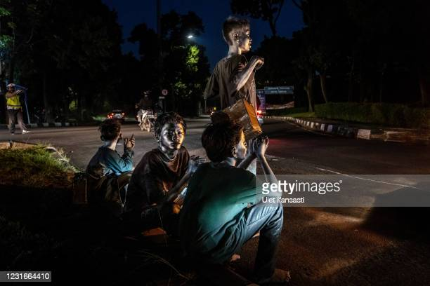 """Children wearing silver paint beg on the street on March 11, 2021 in Depok, Indonesia. 'Silver Men', called """"Manusia Silver"""" in Indonesian language,..."""