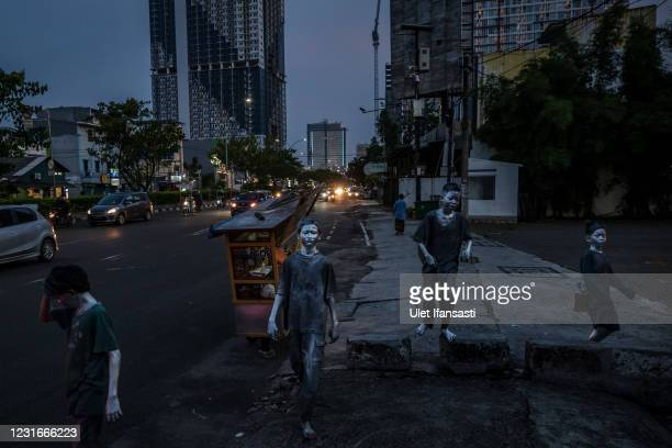 """Children wearing silver paint walk as they beg on the street on March 11, 2021 in Depok, Indonesia. 'Silver Men', called """"Manusia Silver"""" in..."""