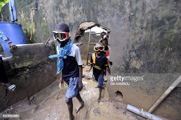 Children wearing ski masks enter a common courtyard with the ground covered by mud on June 19 2014 in a poor neighborhood in the Attecoube commune...