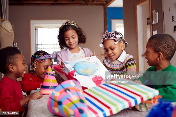Children wearing tiaras and opening gifts