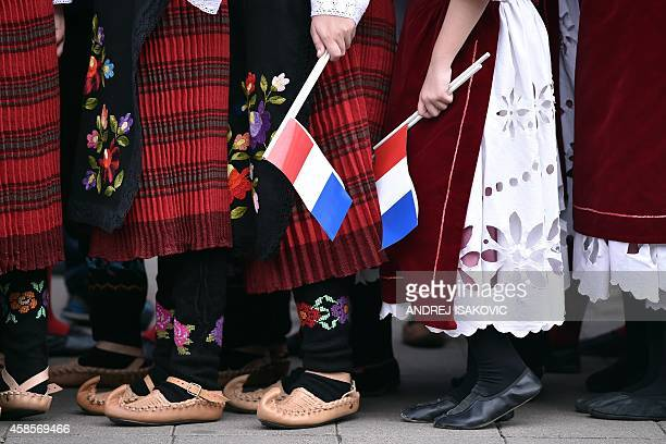 Children wearing traditional Serbian folk costumes await the arrival of the French Prime Minister and his Serbian counterpart in the town of...