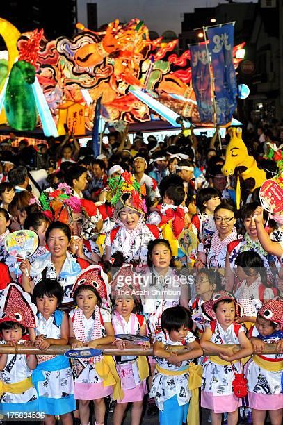 Children wearing traditional summer kimono Yukata march on with Illuminated floats called 'Nebuta' during the Aomori Nebuta Festival on August 2 2013...
