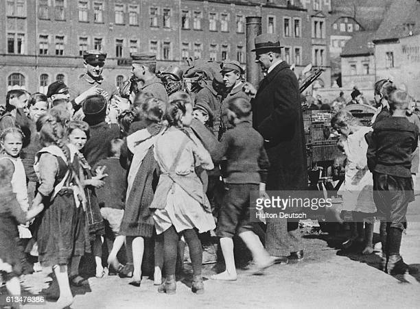 Children welcome German soldiers returning home after the declaration of the Armistice 1918