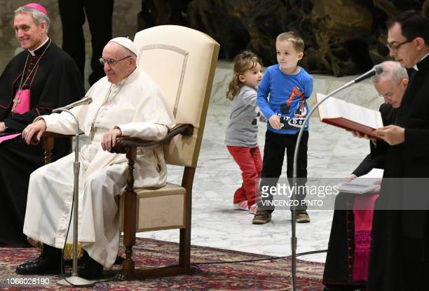 Children who came from the audience play on the stage behind Pope Francis and Prefect of the Papal Household Georg Ganswein during the weekly general...
