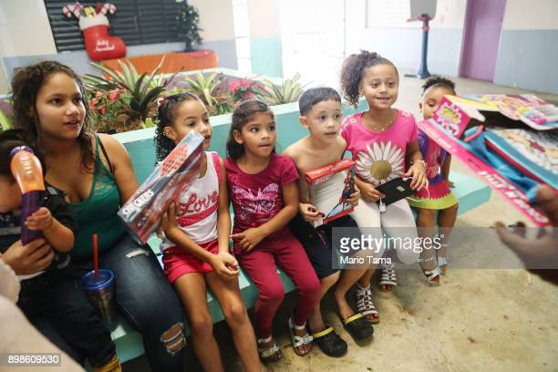 Children who currently reside in a shelter for Hurricane Maria victims wait to receive Christmas presents donated by a local church on December 25...