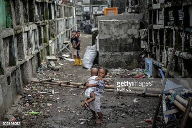 Children who reside in the area play next to stacked graves at the municipal cemetery of Navotas city, north of Manila, Philippines, October 28,...